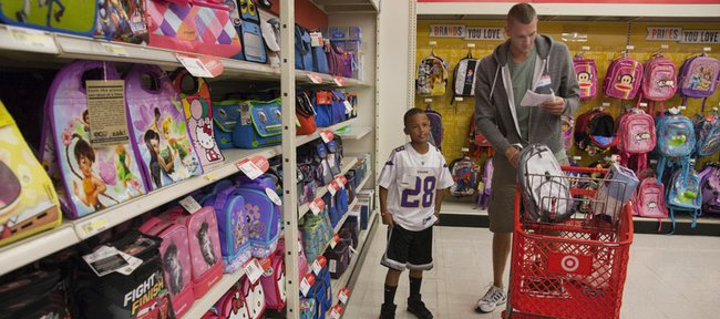 Oklahoma City Thunder center and former Kansas University player Cole Aldrich, right, checks a list of school supplies he planned on buying for Isaiah Mayo, 8. Aldrich and Target purchased $1,000 worth of school supplies for city youths Monday at SuperTarget, 3201 Iowa Street.