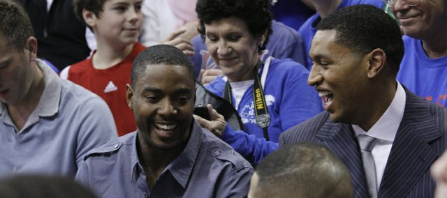 Former KU players and teammates Aaron Miles, left, and Wayne Simien watch the Jayhawks during the second half of their game against the Kansas State Wildcats, Saturday, Jan. 29, 2011 at Allen Fieldhouse. Simien had his jersey retired in a halftime ceremony at the game.