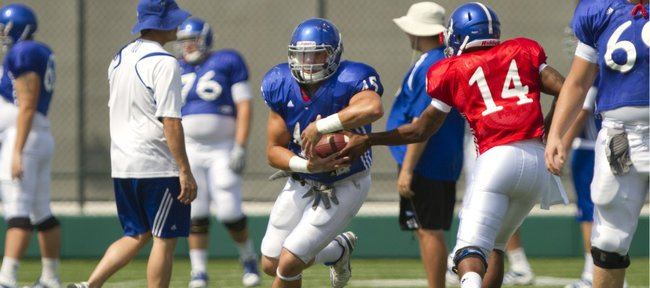 Kansas fullback Nick Sizemore takes a handoff from quarterback Mike Cummings during practice on Tuesday, Aug. 23, 2011.