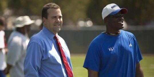 Kansas athletic director Sheahon Zenger hangs out with head coach Turner Gill on the sidelines of practice on Tuesday, Aug. 16, 2011.
