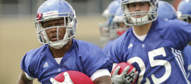 Kansas running back Darrian Miller works through drills during the team's first practice on Thursday, Aug. 4, 2011. In back is freshman running back Brandon Bourbon.