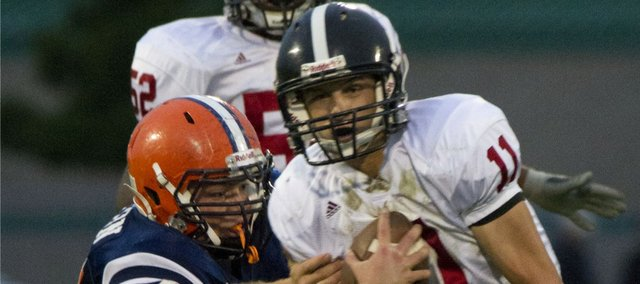 Lawrence High quarterback Brad Strauss (11) runs past Olathe East's Myron Tipton on Friday, Sept. 16, 2011 in Olathe.