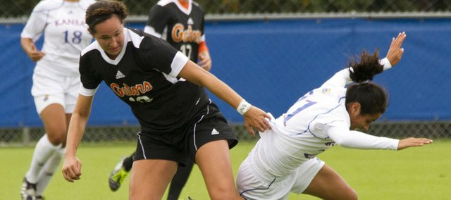 Florida's Holly King, left, takes the ball as she knocks Kansas University's Liana Salazar off balance Sunday, Sept. 18, 2011 at KU.