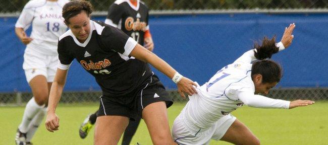 Florida's Holly King, left, takes the ball as she knocks Kansas University's Liana Salazar off balance Sunday, Sept. 18, 2011 at KU.