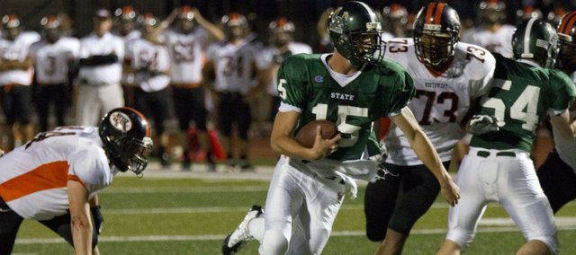 Free State quarterback Kyle McFarland runs through a hole in the Shawnee Mission Northwest defense on his way to a touchdown Friday, Sept. 23, 2011 at FSHS.