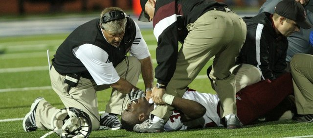 Lawrence High School head football coach Dirk Wedd comforts senior running back Charles Jackson after an injury late in the fourth quarter Friday, Sept. 23, 2011 in Leavenworth.