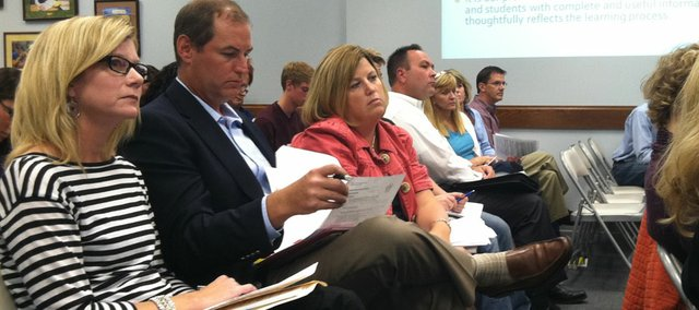 Jill Patton, left, joins more than 80 people in attending a Lawrence school board meeting that included a discussion of standards-based grading for sixth-graders in Lawrence middle schools. Patton was among those opposed to the use of such grades. The meeting was Sept. 26, 2011, at district headquarters, 110 McDonald Drive.