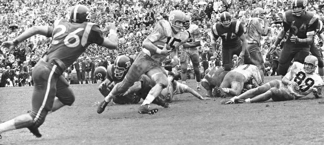Kansas quarterback Rodger McFarland (15) picks his path as he skips along for a 13-yard touchdown run in the final period of their Bluebonnet Bowl game with Rice at Houston, Dec. 16, 1961. Kansas won, 33-7. Others in the play are: John Cornett (74), Dickie Woods (64) of Rice and Jay Roberts (89) of Kansas. (AP Photo)