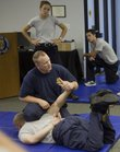 Lawrence police officer Chris Wech demonstrates a defensive position on Sgt. Kirk Fultz for new recruits during a defensive tactics class Thursday, Sept. 29, 2011.