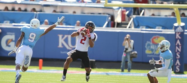 Texas Tech receiver Cornelius Douglas catches a deep pass between Kansas defenders Keeston Terry (9) and Tyler Patmon (33) during the second quarter on Saturday, Oct. 1, 2011 at Kivisto Field.