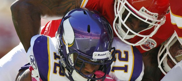 Minnesota Vikings wide receiver Percy Harvin (12) is tackled by Kansas City Chiefs cornerback Brandon Carr and outside linebacker Tamba Hali during the first half of an NFL football game at Arrowhead Stadium in Kansas City, Mo., Sunday, Oct. 2, 2011. (AP Photo/Ed Zurga)