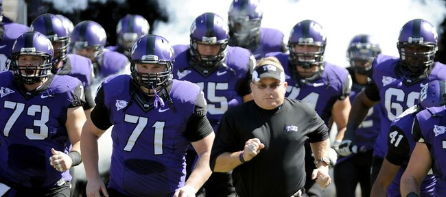 In this photo taken Saturday, Oct. 1, 2011, TCU head coach Gary Patterson runs onto the field with his team before a game against SMU in Fort Worth, Texas.