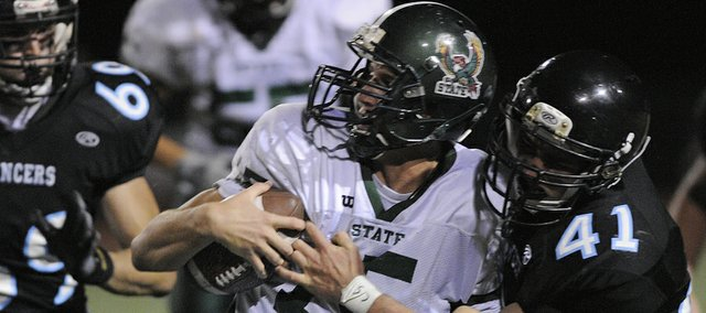 Free State quarterback Kyle McFarland is wrapped up by the defense as Free State played Shawnee Mission East Thursday, Oct. 6, 2011, in Overland Park.