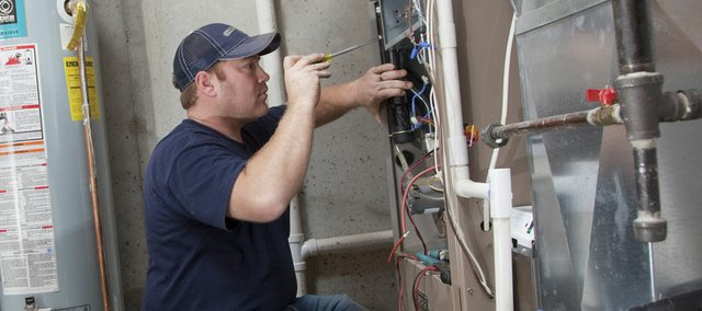 Chad Hull, a service technician with Cloud Heating, makes a service inspection on a home gas furnace in this 2009 file photo. Despite recent warm weather, experts say that it's never too early to consider safety regarding heating your home.