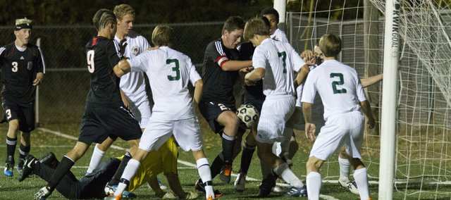 Lawrence High and Free State players crowd the goal as LHS' Justin Riley, center, uses his knee to knock the ball in the goal during Free State's soccer match against Lawrence High Thursday, Oct 13, 2011 at FSHS. Although Riley got the ball into the goal, the goal was waved off and a yellow card was issued. The game ended in a 0-0 tie following two overtime periods.