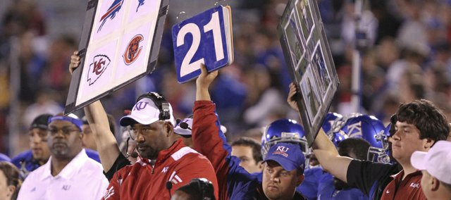 Image boards featuring NFL icons are held up from the Kansas bench during Saturday's home game against Oklahoma as what was later explained to be an attempt to simplify the play calling.