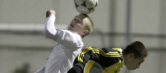 Lawrence High's Connor Henrichs, left, knocks the ball away from a Shawnee Mission West player Tuesday, Oct. 18, 2011.