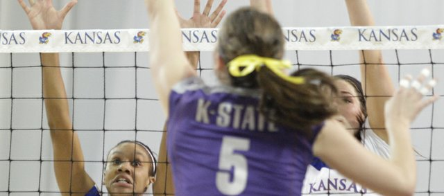 Kansas players Tayler Tolefree (5) and Allison Mayfield (15) rise up to attempt a block against Kansas State's Kathleen Ludwig during the second set on Wednesday, Oct. 19, 2011 at the Horejsi Center.