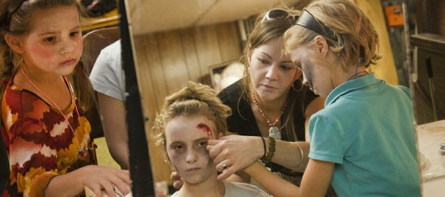 Reflected in the mirrors. Lily Otter, 6, left, watches as Ellea Wilson, 10, center, gets a bloody cut applied to her forehead with the help of her sister, Aya Wilson, 8, and Hailey Gillespie, the youth education director with Theatre Lawrence.