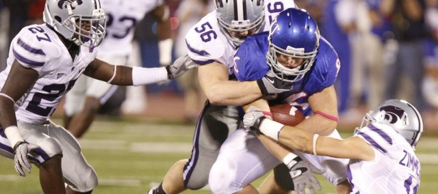 Kansas tight end Tim Biere is brought down by Kansas State defenders David Garrett (27), Alex Hrebec (56) and Ty Zimmerman (12) during the second quarter, Thursday, Oct. 14, 2010 at Kivisto Field. A Nebraska native, Biere quickly learned the importance of the yearly KU-Kansas State game.