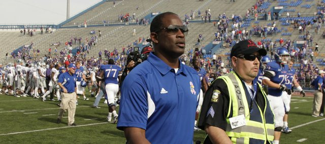 Kansas head coach Turner Gill is escorted by security from the field following the Jayhawks' 59-21 loss to rival Kansas State on Saturday, Oct. 22, 2011 at Kivisto Field.