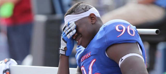 Kansas defensive end Keba Agostinho holds his head on the Kansas bench during the fourth quarter against Kansas State on Saturday, Oct. 22, 2011 at Kivisto Field.