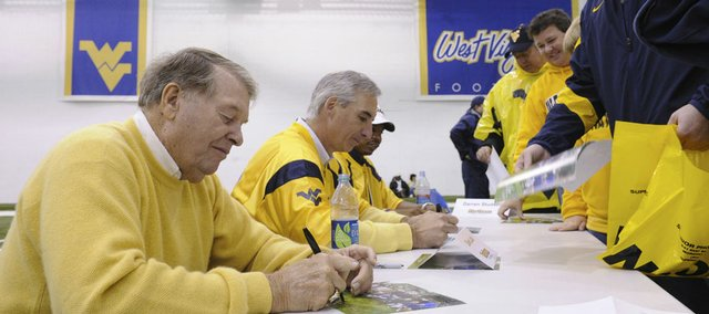 Former West Virginia coach Don Nehlen signs a print for Steve Sites at the Caperton indoor facility before an NCAA college football game between West Virginia and Bowling Green on Saturday, Oct. 1, 2011, in Morgantown, W.Va.