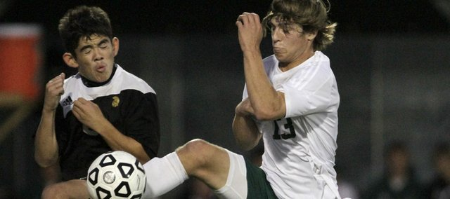 Free State's Caleb Francis (13) leaps for the ball against Topeka High on Tuesday, Oct. 25, 2011.