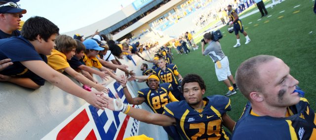 In this Oct. 8, 2011 file photo, West Virginia running back Dustin Garrison (29) leads a group of players thanking fans after their win over Connecticut in Morgantown. The Big 12 has approved West Virginia as an addition to its conference.