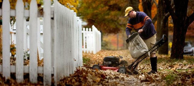 Like many, Lawrence resident Steve Birchfield is finishing last-minute yard work before he packs his mower away for the winter in the Journal-World file photo. Small, preventative measures such as draining the mower of its gas or sharpening its blades before putting it away go a long way toward extending the life of the mower and avoiding costly repairs.