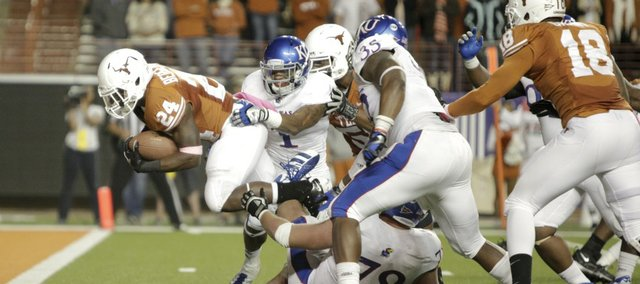 Kansas safety Lubbock Smith (1) and the Jayhawk defense can't hold back Texas running back Joe Bergeron as he marches through for a touchdown during the third quarter on Saturday, Oct. 29, 2011 at Darrell K Royal-Texas Memorial Stadium.