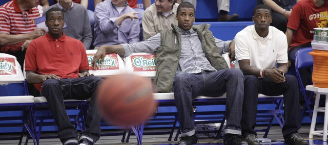 Kansas projected starters Tyshawn Taylor, left, Thomas Robinson and Elijah Johnson watch warm-ups prior to KU's game against Pittsburg State on Tuesday, Nov. 1, 2011 at Allen Fieldhouse. Taylor and Johnson were suspended; Robinson is nursing an injury.