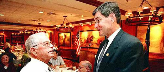Former Kansas University track and cross country coach Bob Timmons, left, enjoys a few moments of conversation with Rep. Jim Ryun, R-Kan., during a Lawrence Chamber of Commerce Luncheon in this 2001 file photo. Timmons will be inducted into the USA Track and Field Hall of Fame.