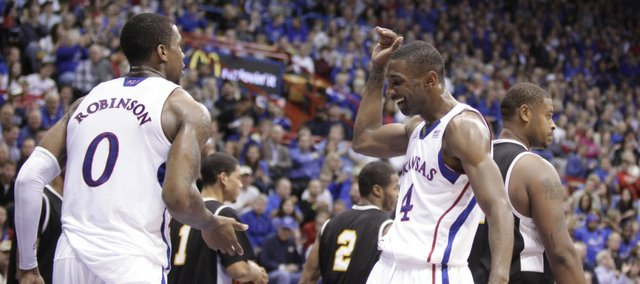Teammates Justin Wesley (4) and Thomas Robinson slap hands after a Robinson converted a bucket and a foul against Fort Hays State during the first half on Tuesday, Nov. 8, 2011 at Allen Fieldhouse.