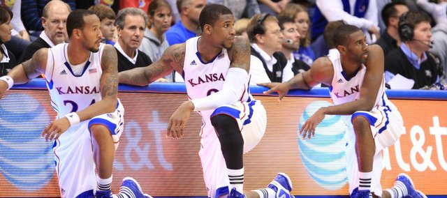 Kansas teammates Travis Releford, left, Thomas Robinson and Justin Wesley strike a similar pose as the three wait to check into the game against Fort Hays State during the first half on Tuesday, Nov. 8, 2011 at Allen Fieldhouse.
