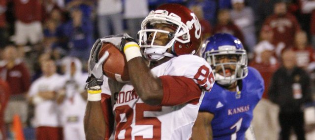 Oklahoma receiver Ryan Broyles catches a touchdown pass past Kansas safety Lubbock Smith during the third quarter on Saturday, Oct. 15, 2011 at Kivisto Field.