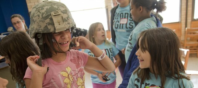 Nola Levings, 9, and Eliana Delcampo, 8, take turns trying on a Marine Corps helmet during a Strong Girls program Wednesday during which girls got to meet and hear from four female military veterans at Kansas University's sport and exercise psychology department. Strong Girls is a Kansas University-affiliated after-school program.