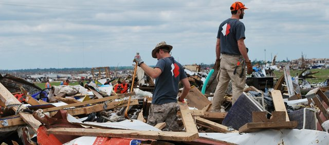 Team Rubicon members Tyler Tannahill and Tom Hudson search debris in Joplin, Mo., after a tornado devastated the town.