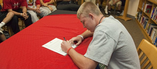 Lawrence High senior Garrett Cleavinger made it official in front of friends and family in the school library Wednesday when he signed to play baseball for the Oregon Ducks.