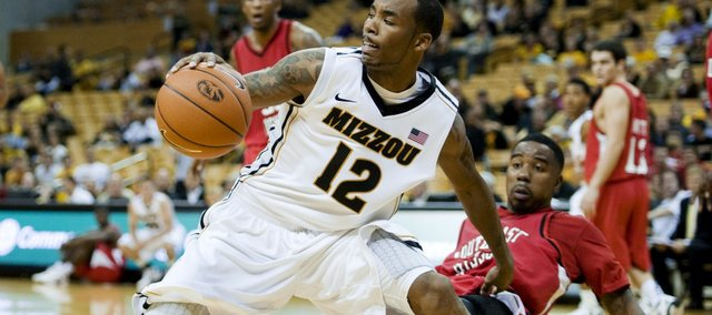 Missouri's Marcus Denmon, left, holds on to the ball as Southeast Missouri State's Marland Smith, right, falls back as he defends during the second half Friday, Nov. 11, 2011, in Columbia. Mo. Missouri won the game, 83-68.