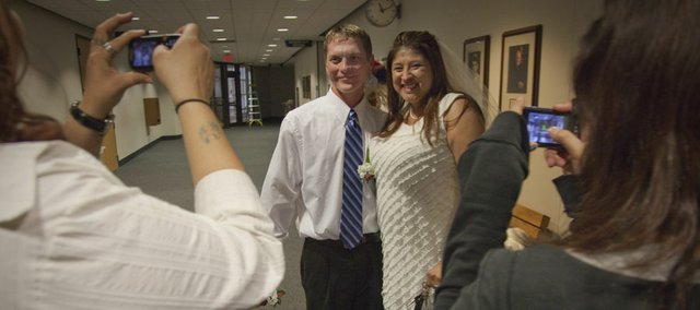 Joel Carbough and Felicia Hernandez, both of Lawrence, smile for family snapshots after they just got married Friday, Nov. 11, 2011, at the Douglas County Judicial and Law Enforcement Center at 111 E. 11th St. The officially tied the knot at 11:11 a.m.