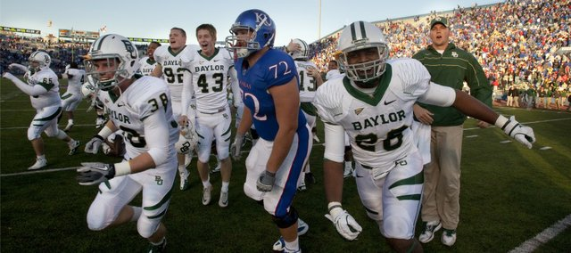Kansas offensive lineman Tanner Hawkinson finds himself in the middle of a rush of Baylor Bears as they celebrate their overtime win after a failed two-point conversion by the Jayhawks on Saturday, Nov. 12, 2011 at Kivisto Field.