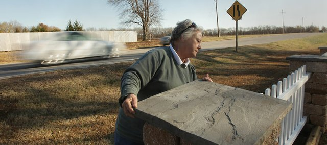 Setting a cap stone on her fence, Kathy Shuck, Pleasant Grove, has rebuilt her fence some 30 times due to vehicles damaging it.