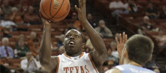 Texas' J'Covan Brown (14) shoots in front of Rhode Island's Nikola Malesevic (23) during the first half of an NCAA college basketball game Tuesday, Nov. 15, 2011, in Austin, Texas.