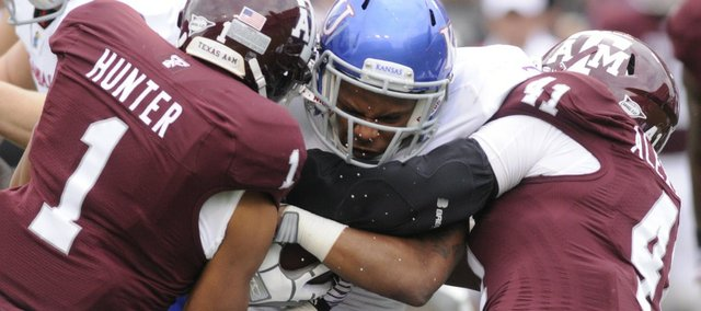 Kansas running back Darrian Miller is squeezed by the A&M defense in the first half Saturday, Nov. 19, 2011 at Kyle Stadium in College Station, Texas.