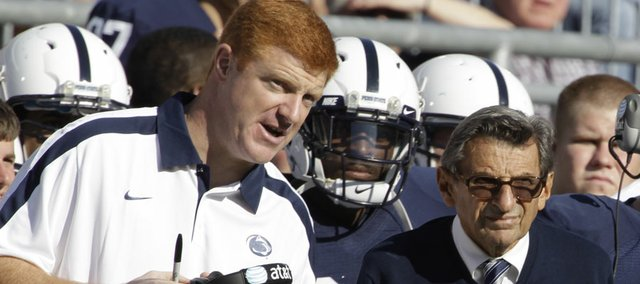 In this Oct. 8, 2011 file photo, Penn St. assistant football coach Mike McQueary, left, talks with head coach Joe Paterno during an NCAA college football game against Iowa, in State College, Pa. McQuery has been heavily criticized for not contacting authorities after witnessing former Penn State assistant coach Jerry Sandusky allegedly raping a child.