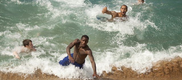 Kansas guards Tyshawn Taylor, left of center, Travis Releford and team video coordinator Doug Compton Jr., catch a wave during some free time before practice on Sunday, Nov. 20, 2011 on Kaanapali Beach in Lahaina. The Jayhawks take on Georgetown Monday night during the Maui Invitational.