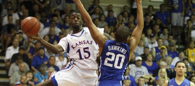 Kansas guard Elijah Johnson elevates to pass along the baseline as he is defended by Duke guard Andre Dawkins during the first half Wednesday, Nov. 23, 2011 at the Lahaina Civic Center.