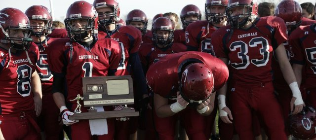 Eudora's Austin Searight (1) is surrounded by dejected Cardinal teammates, holding the consolation trophy after the a 21-0 loss to Rose Hill in the 4A state football championship game Saturday, Nov. 26, 2011 in Salina.