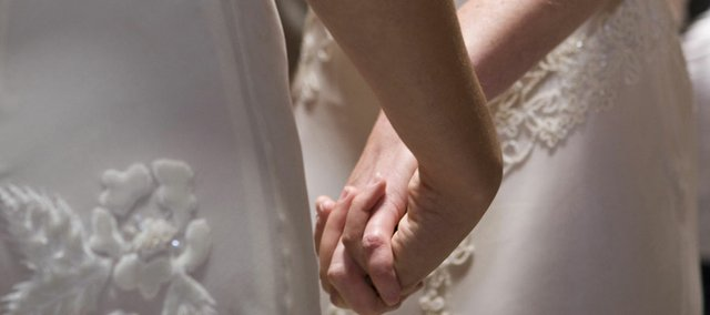 In this 2008 file photo, Amber Weiss and Sharon Papo, both of Berkeley, Calif., hold hands during their wedding ceremony at City Hall in San Francisco. Advocates are now seeking to repeal a Kansas law which classifies homosexual sex is a criminal offense.